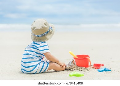 Asian 9 months baby boy playing on the sandy summer beach near the sea. Summer, Travel, Holiday concept