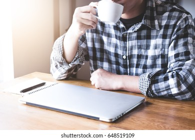 Asian accountant working on laptop while sitting in a cafe.