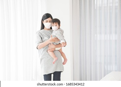 Asian active mother and cut baby Wearing a hygienic mask prevent covid-19 in white room
