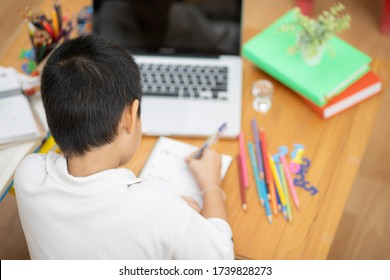 Asian adorable boy be happy and smiling use laptop computer to work at home.Boy sitdown at living room.Social distancing for study online at home lifestyle.