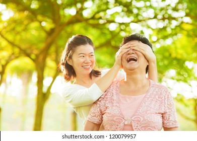 Asian adult daughter covering her senior mother eyes by hands at outdoor park