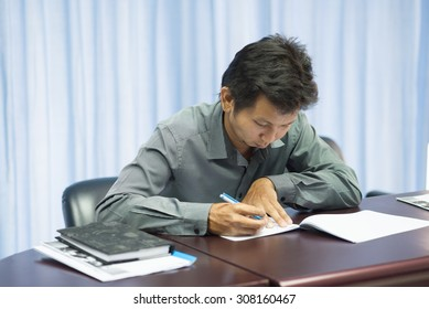 Asian adult education student struggles with test axam as anxiety as he takes an exam