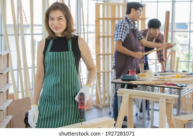 An asian adult female worker wearing black shirt with green stripe apron stand smiling and holding red electric screwdriver when her male colleagues wearing plaid shirt discussing behind at wooden