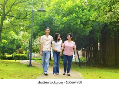 Asian adult having a outdoor walk with senior mother