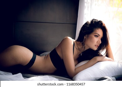 Asian adult sexy lady in black bikini lie on a pillow in the bedroom