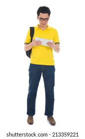 Asian adult student in casual wear with school bag using digital computer tablet pc standing isolated on white background. Asian male model.