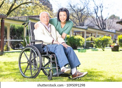 Asian and african nurses helping elder man on wheelchair at rehab facility garden.