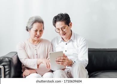 Asian aged couple using a tablet at home