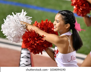 Asian American Cheerleader performing at a High School Football Game