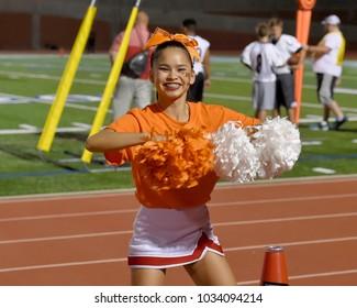 Asian American Cheerleader performing at a High School Football Game