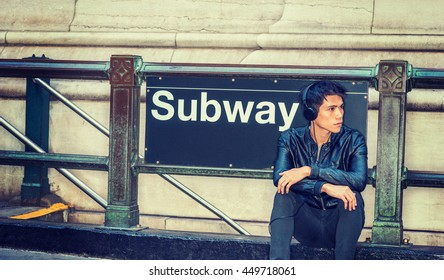 Asian American college student traveling, studying in New York. Wearing black leather jacket, headphone, a guy sitting on street against Subway station sign, listening music. Instagram filtered effect