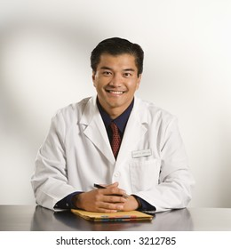 Asian American male doctor sitting at desk with charts smiling and looking at viewer.