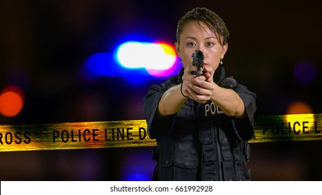 Asian American Policewoman pointing a pistol with siren and boundary tape in background