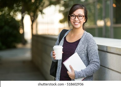 Asian american university student smiling with coffee and book bag on campus with print space