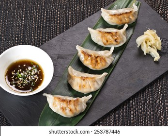 Asian appetizer menu fried dumplings with soy sauce on stone black plate