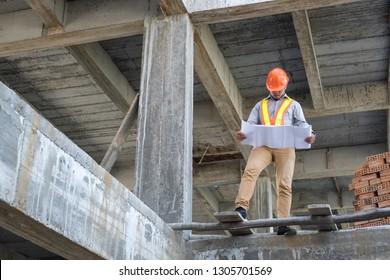 Asian architect or engineer holding looking project blueprint papers and wear helmet at construction site.