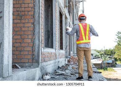 Asian architect or engineer holding looking project blueprint papers and wear helmet at construction site. Back view.
