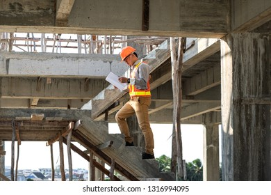 Asian architect or engineer holding looking project blueprint papers and wear helmet at construction site. He walking on stairs.