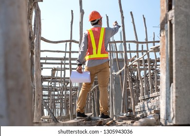 Asian architect or engineer holding project blueprint papers and wear helmet at construction site. He pointing forward and up. Back view.