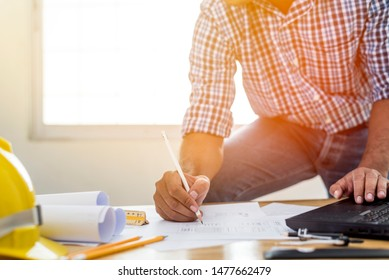 Asian architect man Standing working with blueprints sketching a construction project on wood desk at home office.Construction design concept.