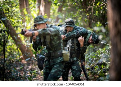 Asian army soldier with weapon during rescue operation carry a wounded soldier evacuate at across the deep forest.