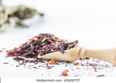 Asian aromatic tea ingredients and herbs isolated on white background with wooden spoon and ceramic bowl