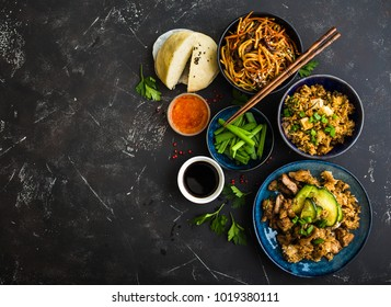 Asian assorted food set, dark rustic stone background. Chinese dishes. Chinese stir-fry noodles, asian rice with meat, dim sum, snacks, steamed Chinese buns. Space for text. Top view. Asian style