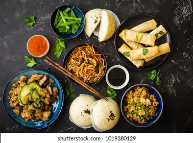 Asian assorted food set, dark rustic stone background. Chinese dishes. Chinese stir-fry noodles, asian rice with meat, dim sum, fried spring rolls, steamed Chinese buns. Top view. Asian stile dinner