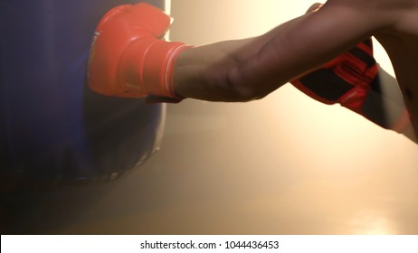Asian athlete boxer punching a punching bag with effect dramatic lighting in studio. Young professional boxer training with punching bag in gym on dark background with spotlight and smoke