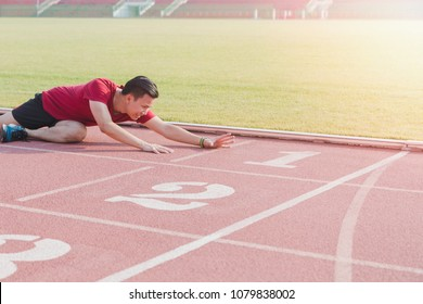 Asian athletes sport man falls down and reaches the finish line on running track while exercising.Concept of people hard work with sport activity.