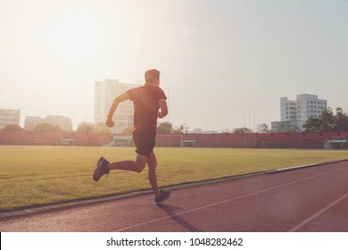 Asian athletes sport man running on track in stadium at morning.Concept of people exercise activity.Vintage tone.