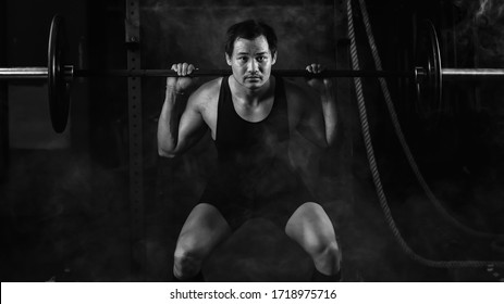 asian athletic strong man having workout and bodybuilding with barbells weightlifting backsquat style in gym and fitness center in dark tone black and white
