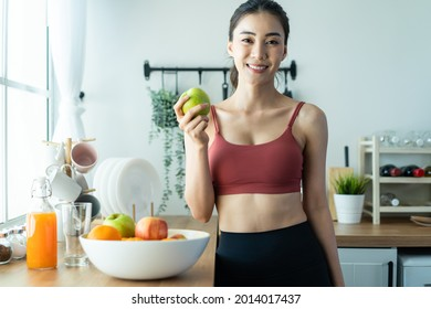 Asian attractive active woman pick up a green apple in kitchen at home. Beautiful sport girl in sportswear desire to chose fruit and ignore sweet donut enjoy eat healthy food for health after exercise