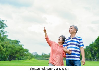 Asian attractive happy senior couples walking away in the green park or garden. Grandmother point to something and told grandfather to look at it.