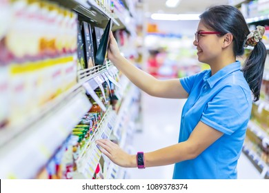 Asian attractive happy woman choosing and reading food labels with ingredients on a box from its shelf at the supermarket or convenience store.