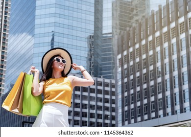 Asian attractive smile beautiful shopaholic woman look forward to continue shopping at next department store and walking on skywalk in metro station at shopping center area