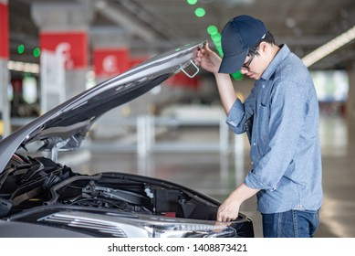 Asian auto mechanic checking car engine under the hood in auto service garage. Mechanical maintenance engineer working in automotive industry. Automobile servicing and repair