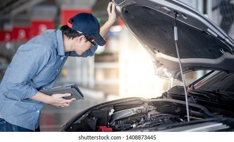 Asian auto mechanic holding digital tablet checking car engine under the hood in auto service garage. Mechanical maintenance engineer working in automotive industry. Automobile servicing and repair