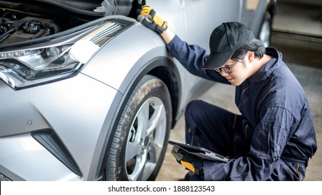Asian auto mechanic holding digital tablet checking car wheel and tire in auto service garage. Mechanical maintenance engineer working in automotive industry. Automobile servicing and repair concept - Shutterstock ID 1888123543