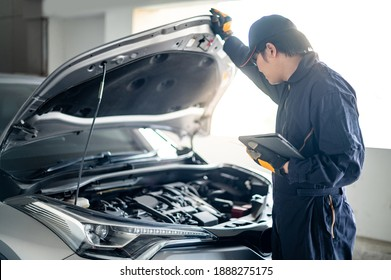 Asian auto mechanic holding digital tablet checking car engine under bonnet hood in auto service garage. Mechanical maintenance engineer working in automotive industry. Automobile servicing and repair