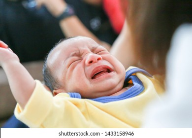 Asian babies in yellow dresses are crying because they want to eat breast milk. The mother is carrying a baby who is crying.