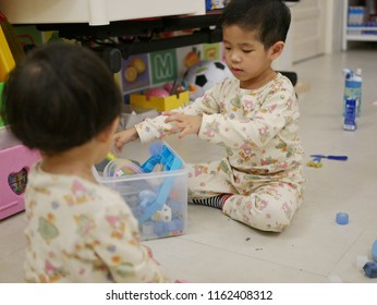 Asian baby, 31 months old, (right) is cleaning up / putting away toys she played with her little sister