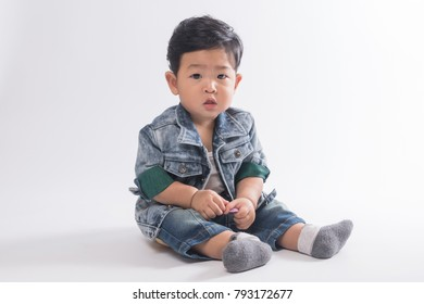 Asian baby boy 8 months old sitting on shade white background