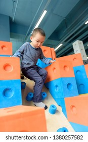 Asian baby boy climbing down from  plastic blocks toys in indoor playground