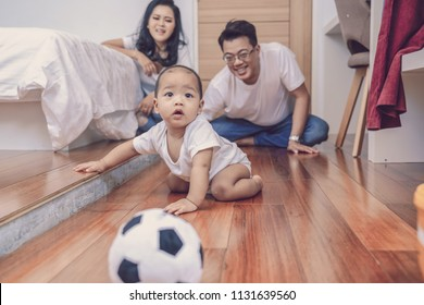 Asian baby boy crawl on the wooden floor over the father and mother in the bedroom,Family Lifestyle Concept