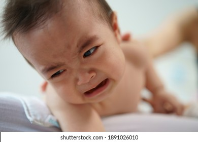 Asian baby  boy crying on bed with hold by mother hand in bedroom. Portrait of cute little son crying on bed at home.