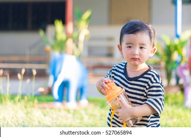 Asian baby boy drink with water bottle at outdoor playground, school yard shallow DOF
