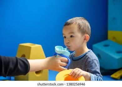 Asian baby boy drinking water in indoor playground