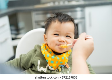 Asian baby boy eating blend food on a high chair