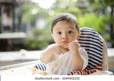 Asian baby boy eating with baby led weaning (BLW) method, soft focus